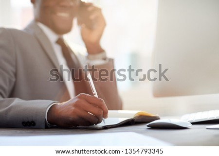 Hand of young contemporary broker holding pen over notebook page while making notes and calling clients #1354793345