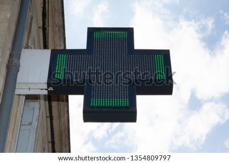 Pharmacy green cross sign in street shop #1354809797