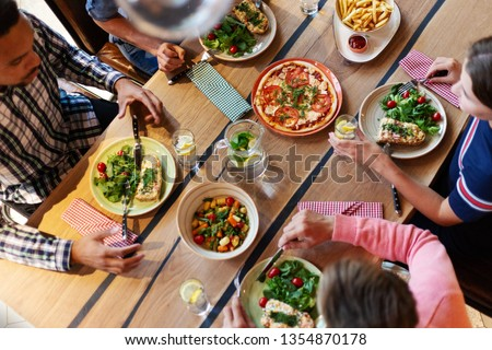 From above view of four friends having dinner at wooden table with homemade food and drinkson it #1354870178