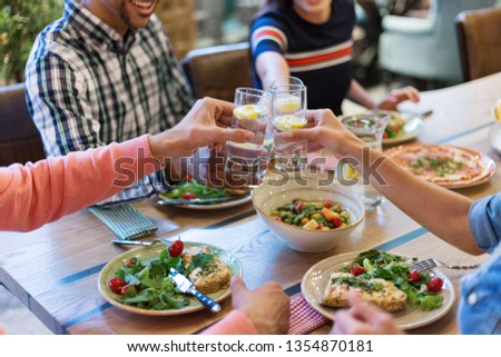 Cropped four friends sitting at wooden table and toasting during dinner party #1354870181