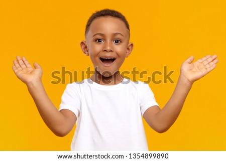 I'm so happy. Picture of overjoyed excited black little boy of African origin exclaiming emotionally and gesturing actively with both hands, amazed with good news, receiving highest mark for test