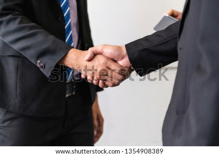 Business people agreement concept. Businessman do handshake with another businessman in the office meeting room. #1354908389