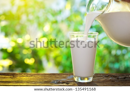 Pouring milk in the glass on the background of nature. Royalty-Free Stock Photo #135491168