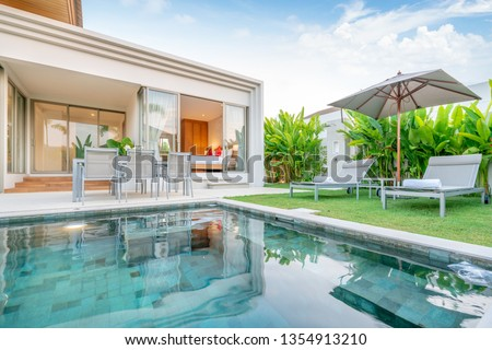 home or house Exterior design showing tropical pool villa with greenery garden, sun bed, umbrella, pool towels #1354913210