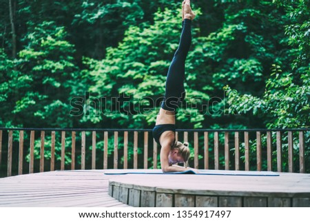 Sportive female athlete spending time for morning yoga standing in sarvangasana and enjoying healthy lifestyle, young slim woman doing shoulder stand on mat for training in nature environment #1354917497