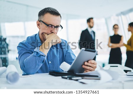 Pondering 50 years old male entrepreneur in trendy eyewear reading received email with bad news about finance problems feeling puzzled on solving, concept of technology and communication #1354927661