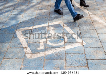 Free space Handicapped parking spot in motel or apartment, transportation infrastructure road markings, people walk in the background