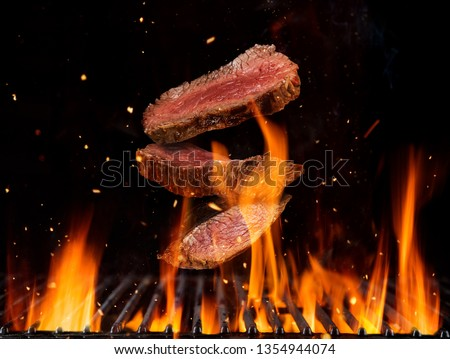 Flying raw beef steaks pieces above burning grill grid, isolated on black backround. Barbecue and grill concept #1354944074