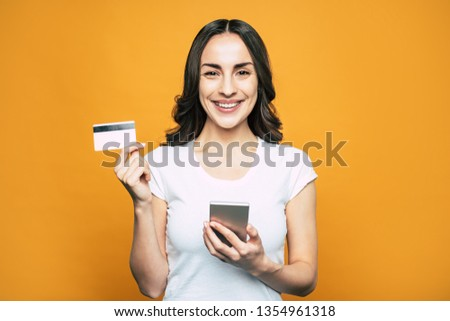 Check card. Bodacious girl with hazel eyes, slightly curled hair and such a brilliant smile in front of flamboyant orange background is holding her phone and a bank card. #1354961318