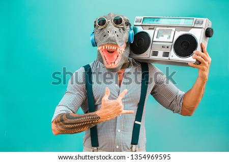 Crazy senior man dancing rock music wearing t-rex mask - Tattoo trendy guy having fun listening music with boombox stereo - Absurd and funny trend concept - Focus on face #1354969595