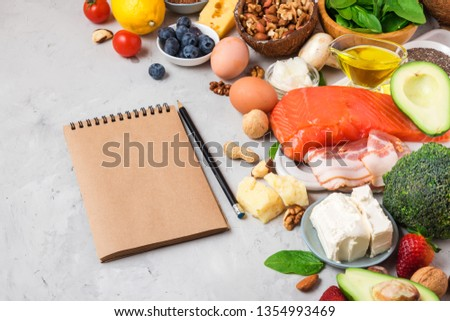 ketogenic diet food. Healthy low carbs products. Keto diet concept. Vegetables, fish, meat, nuts, seeds, berries, cheese with paper notebook on concrete background #1354993469