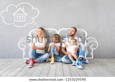 Happy family with two kids playing into new home. Father, mother and children having fun together. Moving house day and real estate concept #1355029598