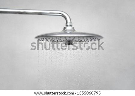 Water running from shower head and faucet in modern bathroom. Rain Shower turned, ceiling shower head closeup in the shower stall.  #1355060795