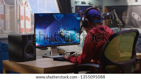 Medium shot of a boy playing with a first-person shooter video game #1355095088