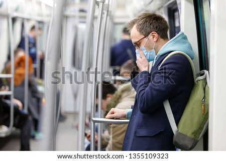 Ill man in glasses feeling sick, coughing, wearing protective mask against transmissible infectious diseases and as protection against the flu in public transport. New coronavirus 2019-nCoV from China Royalty-Free Stock Photo #1355109323