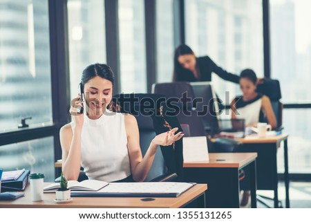 Portrait of a happy business woman sitting at her workplace in office #1355131265