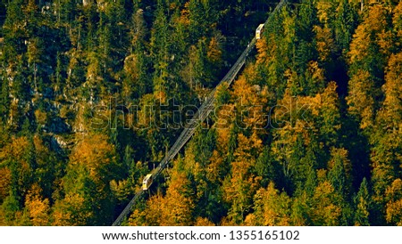Beautiful aerial fall view of cable car ropeway funicular in austrian alps. Red cable railway car in the mountains by resort village Hallstatt, Salzkammergut, Austria, Alps. #1355165102