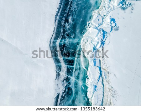 A large crack with bare ice and hummocks passes over the snow-covered surface of Lake Baikal in early spring. View from above. Siberia, Russia #1355183642