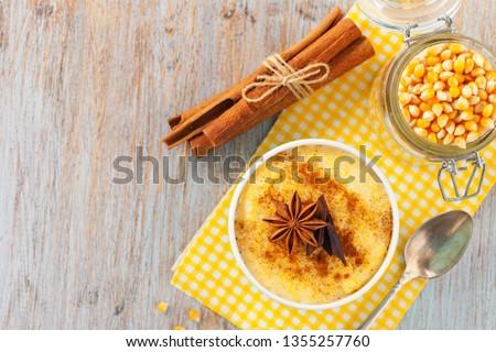 Brazilian sweet custard-like dessert curau de milho mousse of corn with cinnamonon a light background. Corn porridge with cinnamon in a bowl. Top view #1355257760