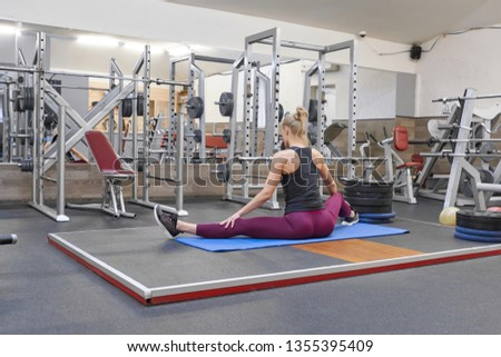 Young athletic muscular woman doing stretching workout in the gym, woman practicing yoga. #1355395409