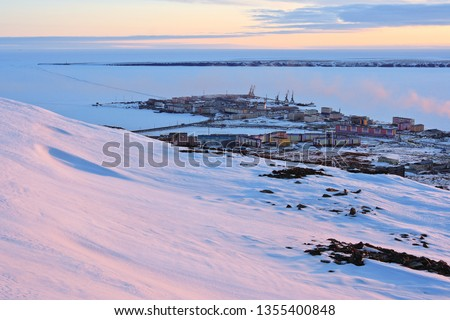 Arctic settlement. Pevek is the northernmost city in Russia. Cold snowy May in the Arctic in the north of Chukotka. Small polar town and the coast of the Arctic Ocean. Pevek, Chukotka, Siberia, Russia #1355400848