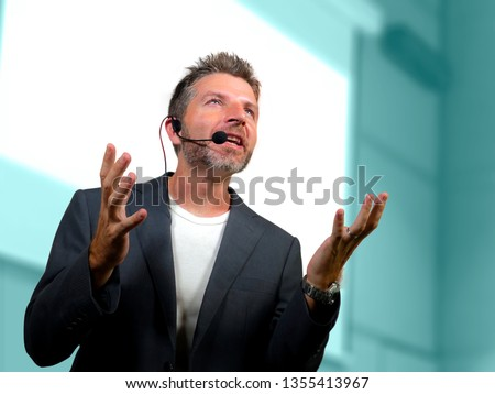 young attractive and confident successful man with headset speaking at corporate business coaching and training auditorium conference room talking giving motivation training from speaker stage #1355413967
