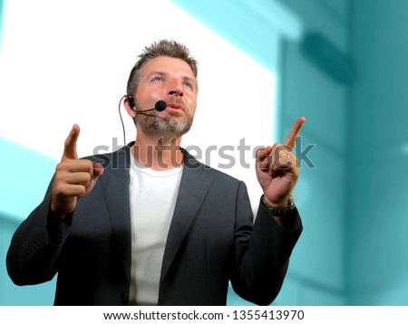 young attractive and confident successful man with headset speaking at corporate business coaching and training auditorium conference room talking giving motivation training from speaker stage #1355413970