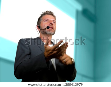 young attractive and confident successful man with headset speaking at corporate business coaching and training auditorium conference room talking giving motivation training from speaker stage #1355413979