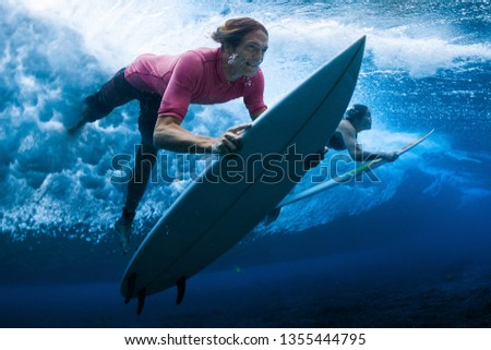 Surfers dive under the breaking wave #1355444795