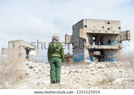 one little child in green jacket standing on ruins of destroyed buildings in war zone Royalty-Free Stock Photo #1355525054