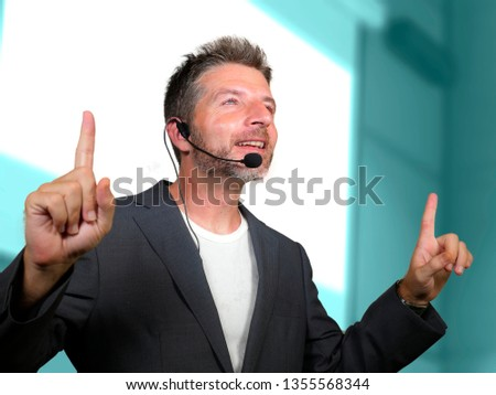 young attractive and confident successful man with headset speaking at corporate business coaching and training auditorium conference room talking giving motivation training from speaker stage #1355568344