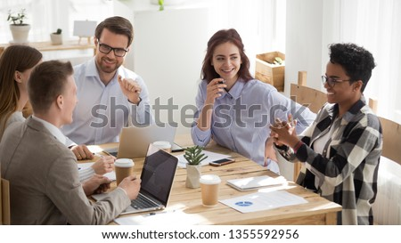 Happy mixed race office workers at business meeting having fun. Diverse men and women laughing sitting at desk, share ideas. Smiling black female speaker talking. Team work, team building concept #1355592956