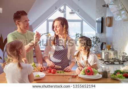 Family with young children cooking together in the kitchen at home #1355652194