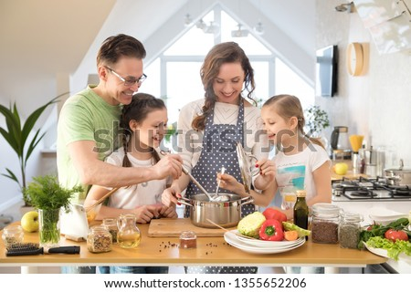 Family with young children cooking together in the kitchen at home #1355652206
