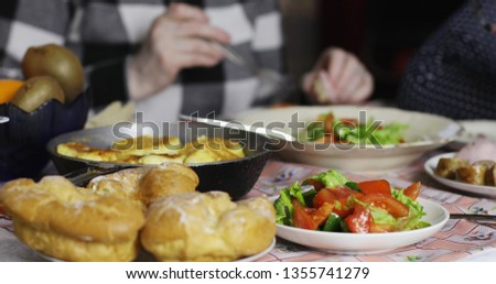 Closeup of an 65 years old woman with glasses sitting at the table and eating. Green salad, pastries lie on the plates. #1355741279