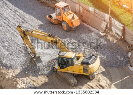 Yellow excavator on rubble working paves the way, next to it is an asphalt stacker #1355802584