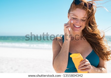 Beautiful young woman at beach applying sunscreen on face. Mature woman with freckles and red hair enjoying summer holiday while applying suntan lotion. Portrait of smiling lady with healthy skin. #1355804342