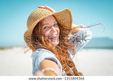 Portrait of beautiful mature woman in casual wearing straw hat at seaside. Cheerful young woman smiling at beach during summer vacation. Happy girl with red hair and freckles enjoying the sun. #1355804366