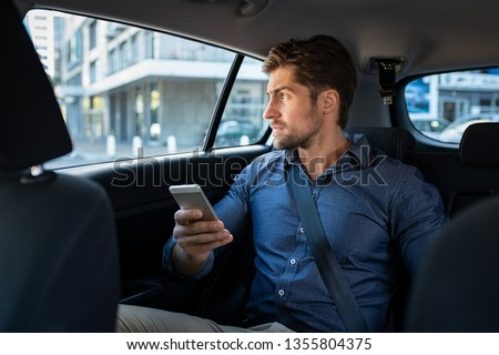 Stressed young businessman sitting in the back seat of car while thinking. Thoughtful business man holding phone sitting in car looking out of window with serious expression. Pensive man in taxi. #1355804375