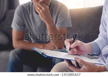 Geriatric doctor or geriatrician concept, Doctor visiting with patient in room and hearing serious disease diagnose writing on clipboard while consulting a man at home   Royalty-Free Stock Photo #1355885657