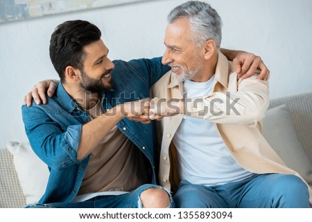 cheerful retired man fist bumping with happy bearded son at home  #1355893094