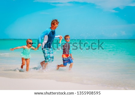 father with kids play with water run on beach #1355908595