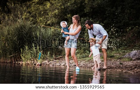 A young family with two toddler children outdoors by the river in summer. #1355929565