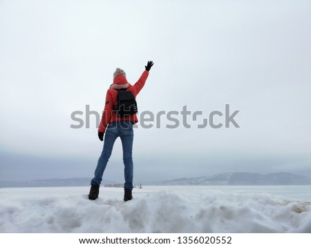 Adult woman traveler waving against the background of the Russian winter landscape #1356020552
