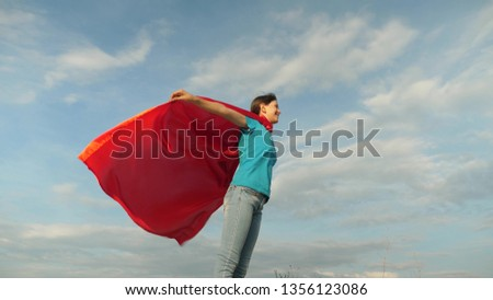 beautiful girl superhero standing on the field in a red cloak, cloak fluttering in the wind. Slow motion. girl dreams of becoming superhero. young girl standing in a red cloak expression of dreams #1356123086