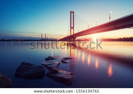 The South bridge at night, Kiev, Ukraine. Bridge at sunset across the Dnieper River. Kiev bridge against the backdrop of a beautiful sunset in Kiev. Bridge in evening sunshine. #1356134765