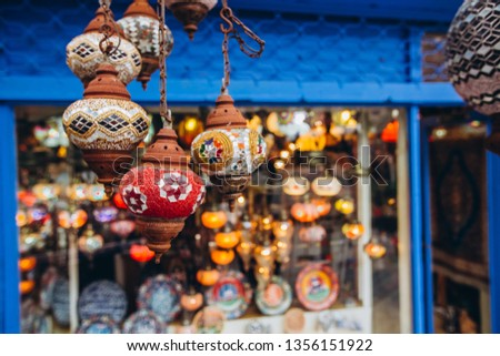 Shopping at the Grand Bazaar. Traditional Turkish lamps in the souvenir shop. Handmade glass mosaic at the Grand Bazaar. Nazar Bonjuk against the evil eye #1356151922
