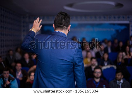 rear view of young successful businessman at business conference room with public giving presentations. Audience at the conference hall. Entrepreneurship club #1356163334