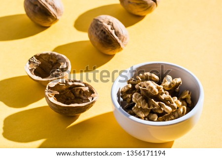 Walnut kernels in a bowl and walnut shells on a yellow table.  Hard light #1356171194