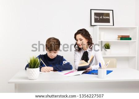 Female teacher helps teen boy to do his homework. Doing homework together. #1356227507